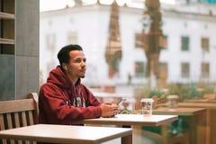 Jeune homme africain s'asseyant à un café et à une musique de écoute de son téléphone portable Image libre de droits