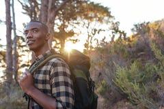 Jeune homme africain seul trimardant dans la région sauvage au crépuscule Photos libres de droits