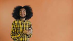 Jeune homme afro-américain attirant heureux utilisant le téléphone et obtenir de bonnes nouvelles sur le fond orange Concept des  clips vidéos