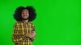 Jeune homme afro-américain attirant heureux utilisant le téléphone et obtenir de bonnes nouvelles sur l'écran vert ou le fond pri banque de vidéos