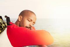 Jeune homme afro-américain beau de hippie détendant sur la plage avec les yeux fermés Verticale de plan rapproché Photo libre de droits