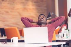 Jeune homme afro-américain d'affaires faisant une pause à son bureau image libre de droits