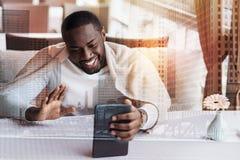 Jeune homme afro-américain heureux parlant avec des amis sur le sien le téléphone Photos stock