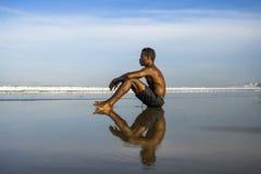Jeune homme afro-américain noir attirant et décontracté avec le corps convenable et le dos musculaire se reposant sur le sable de image stock