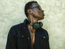 Jeune homme afro-américain sportif beau et attirant dans la veste noire ouverte de denim posant dans l'attitude fraîche dans la b photo stock