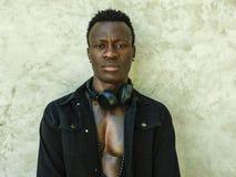 Jeune homme afro-américain sportif beau et attirant dans la veste noire ouverte de denim posant dans l'attitude fraîche dans la b image stock