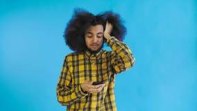 Jeune homme afro-américain triste utilisant le téléphone et la mauvaise nouvelle d'obtention sur le fond bleu Concept des ?motion banque de vidéos