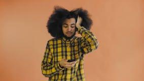 Jeune homme afro-am?ricain triste utilisant le t?l?phone et la mauvaise nouvelle d'obtention sur le fond orange Concept des ?moti banque de vidéos