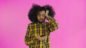 Jeune homme afro-américain triste utilisant le téléphone et la mauvaise nouvelle d'obtention sur le fond pourpre Concept des ?mot banque de vidéos