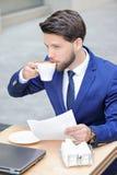 Jeune homme agréable s'asseyant en café Image libre de droits