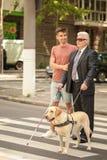 Jeune homme aidant l'homme aveugle avec le chien de guide photos stock