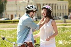 Jeune homme aidant son amie à mettre dessus le casque de bicyclette Photo libre de droits