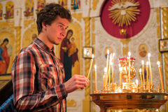 Jeune homme allumant une bougie dans l'église. Photographie stock