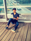 Jeune homme américain asiatique travaillant sur l'ordinateur portable dehors dans N Image stock