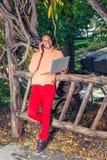Jeune homme américain d'Africain travaillant dehors au parc à New York images stock