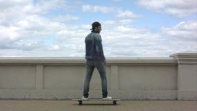 Jeune homme apparaissant dans le cadre et montant une planche à roulettes dans le jour nuageux Image libre de droits