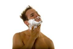 Jeune homme appliquant la crème à raser à son visage Photos libres de droits