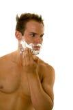Jeune homme appliquant la crème à raser à son visage Photo libre de droits
