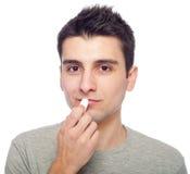 Jeune homme appliquant le baume de languette photographie stock libre de droits