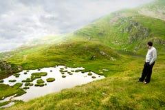 Jeune homme appréciant la haute de vue dans les montagnes Photographie stock