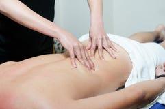Jeune homme appréciant le massage à la station thermale Photos libres de droits