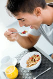Jeune homme appréciant le petit déjeuner dans la cuisine Photo libre de droits