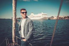 Jeune homme appréciant le tour sur un yacht Image libre de droits