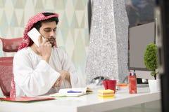 Jeune homme Arabe d'affaires parlant sur le téléphone portable et les finances fonctionnantes au sujet du coût avec l'ordinateur  Images libres de droits