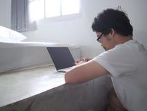 Jeune homme asiatique à l'aide de l'ordinateur portable d'ordinateur dans le salon Internet des choses photo libre de droits