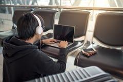 Jeune homme asiatique à l'aide de l'ordinateur portable dans le terminal d'aéroport Images libres de droits