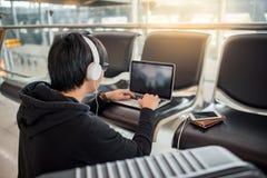 Jeune homme asiatique à l'aide de l'ordinateur portable dans le terminal d'aéroport Images stock
