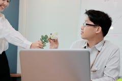 Jeune homme asiatique étonné d'affaires obtenant une rose blanche dans le bureau le jour du ` s de valentine Histoires d'amour da Photos stock