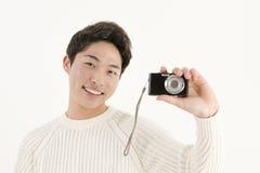 Jeune homme asiatique avec l'appareil photo numérique Photo stock