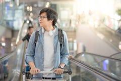 Jeune homme asiatique avec le chariot à aéroport sur l'escalator Photographie stock libre de droits