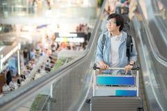 Jeune homme asiatique avec le chariot à aéroport sur l'escalator Images stock