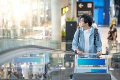 Jeune homme asiatique avec le chariot à aéroport sur l'escalator Photo libre de droits