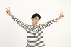 Jeune homme asiatique avec le geste de main de signe de paix de deux doigts Image libre de droits