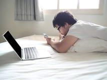 Jeune homme asiatique avec le téléphone intelligent mobile se couchant sur le lit dans le matin Internet de concept de choses photos stock