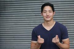 Jeune homme asiatique avec le visage souriant faisant le symbole d'amour avec ses mains d'isolement Images libres de droits