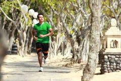 Jeune homme asiatique courant sur l'allée avec des arbres le long, sport Images stock