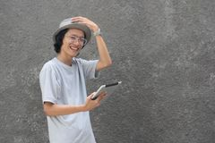 Jeune homme asiatique créatif atractive avec le chapeau et les verres utilisant le comprimé et le sourire de chapeau feutré à la  photographie stock
