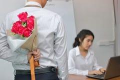 Jeune homme asiatique d'affaires tenant un bouquet des roses rouges derrière le sien de retour pour l'amie dans le jour de valent Image stock