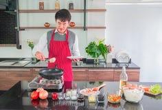 Jeune homme asiatique dans le tablier rouge Cuisson pour la nourriture dans la cuisine à la maison image libre de droits