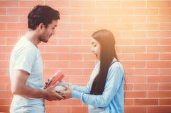 Jeune homme asiatique de couples donnant le boîte-cadeau à la femme dehors Images libres de droits
