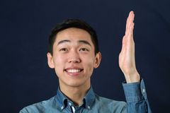 Jeune homme asiatique de sourire jugeant sa main droit et regarder l'upw photos stock