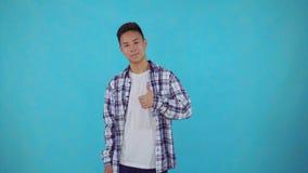 Jeune homme asiatique de sourire montrant des pouces et regarder la caméra au-dessus du fond bleu banque de vidéos