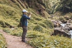 Jeune homme asiatique de voyageur prenant le fond scénique de nature de photo dehors Mode de vie et concept de relaxation photos libres de droits