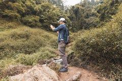 Jeune homme asiatique de voyageur prenant le fond scénique de nature de photo dehors Mode de vie et concept de relaxation images stock
