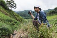 Jeune homme asiatique de voyageur prenant le fond scénique de nature de photo dehors Mode de vie et concept de relaxation image libre de droits