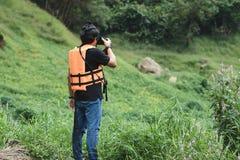 Jeune homme asiatique de voyageur prenant le fond scénique de nature de photo dehors Mode de vie et concept de relaxation photo stock